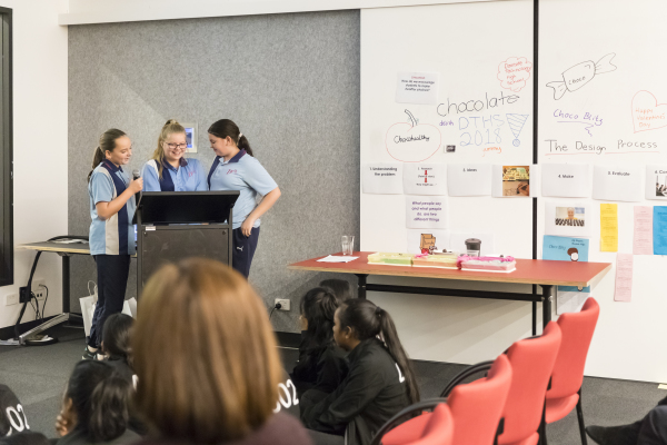 Three young people in school uniform presenting at a lectern, with a display in the background.