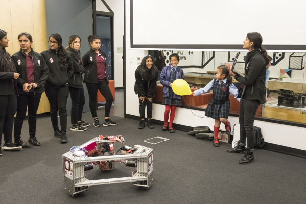 Teenagers showing primary schoolers how to drive a romote-controlled robot.