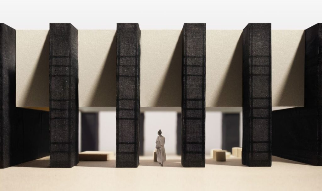Image of an architectural model with columns and a female figure.