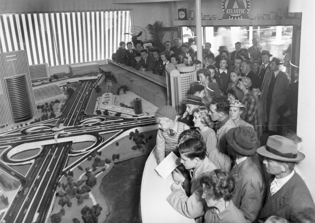 Photograph showing crowds of people in 1947 viewing a model of Sydney as it would appear in the future with freeways, clover leaf intersections and high rise towers.