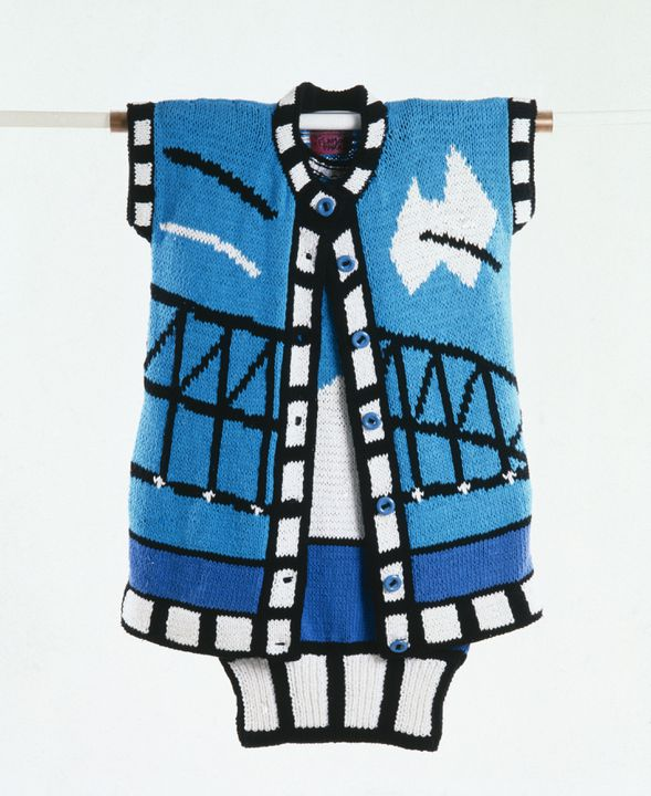 The knitted coat is part of a women's ensemble designed by Jenny Kee and made by Jan Ayres for Flamingo Park. The cardigan-style coat has short sleeves, a round neck, a front buttoning closure and a ribbed band at the bottom. The Sydney Harbour Bridge is depicted in black across the centre front. A stylised white Australia shape, crossed by a black diagonal line, lies on the right breast. Two parallel, diagonal lines, one black, one white, lie on the left breast. A band of blue runs beneath the Bridge representing the sea.