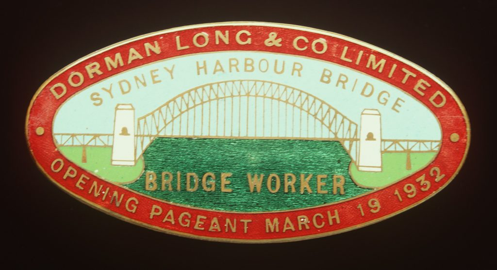 A Sydney Harbour Bridge workers entry badge. The brass badge is oval in shape and has been enamelled in red, blue, green and white. The badge features an image of Sydney Harbour Bridge. The pin on the back of the badge is missing. Text above and below the image of the bridge reads 'SYDNEY HARBOUR BRIDGE / BRIDGE WORKER'. Text in the red border around the image of the bridge reads 'DORMAN LONG & CO LIMITED / OPENING PAGEANT MARCH 19 1932'. Engraved on the back of the badge 'AMOR / SYDNEY'.