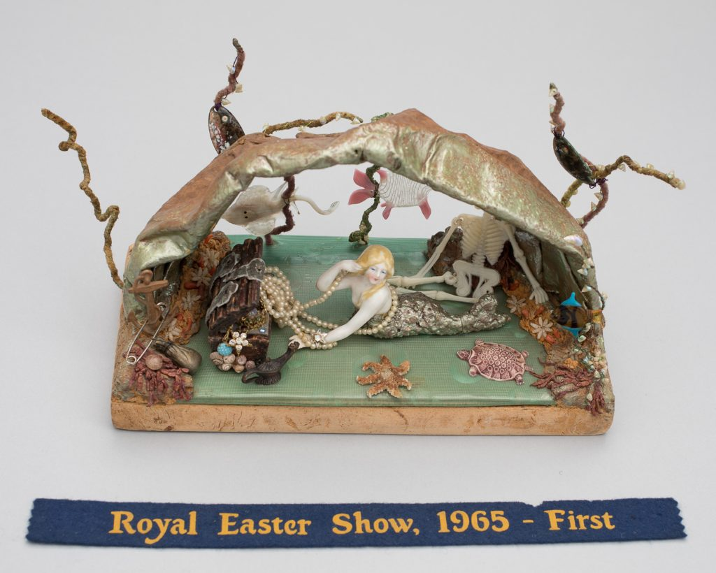 "This doll tableau comprises an underwater cave with reclining ceramic mermaid with long peal necklace surrounded by marine props including a ceramic starfish and turtle, plastic skeleton and jewel-filled treasure chest. The tableau is made of various materials including beadwork, shells, plastic and pipe cleaners. The tableau is mounted on particle board. It has a blue ribbon ""Royal Easter Show 1965 First""."