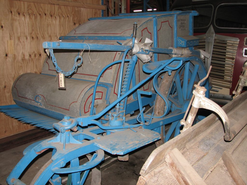 Coloured photograph of a harvester made of metal and finished with red lining and a blue frame. A comb at the front the crop drew it in towards enclosed beaters which removed the heads of wheat and forced it into a large box at the rear. The farmer sat on the harvester while holding the reins of the horses.
