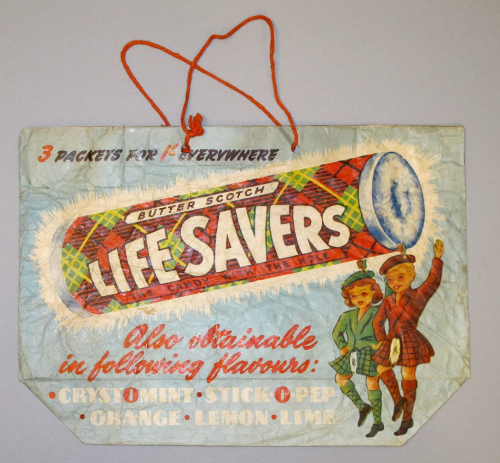 A paper bag with cotton cord handles featuring a coloured picture of a large roll of butterscotch lifesavers and two Scottish girls dancing in kilts.
