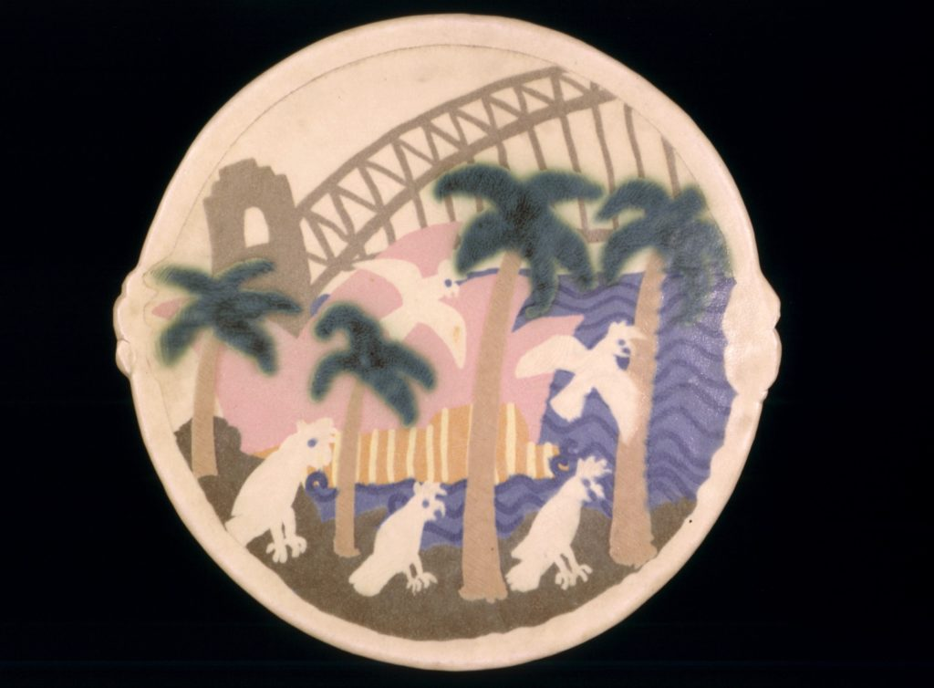 Rounded stoneware platter, unfooted flat base flaring to a shallow bowl with two small protruding handles at each side. The platter features a light coloured stoneware body, decorated under the glaze with a Sydney harbour scene, the Opera House (in pink), palm trees in grey and blue and reserve colouredcockatoos in the foreground with the Sydney Harbour Bridge painted in grey in the background. An undecorated border frames the image. The glaze is a light grey/buff, crackled and opaque in parts for decorative effect.