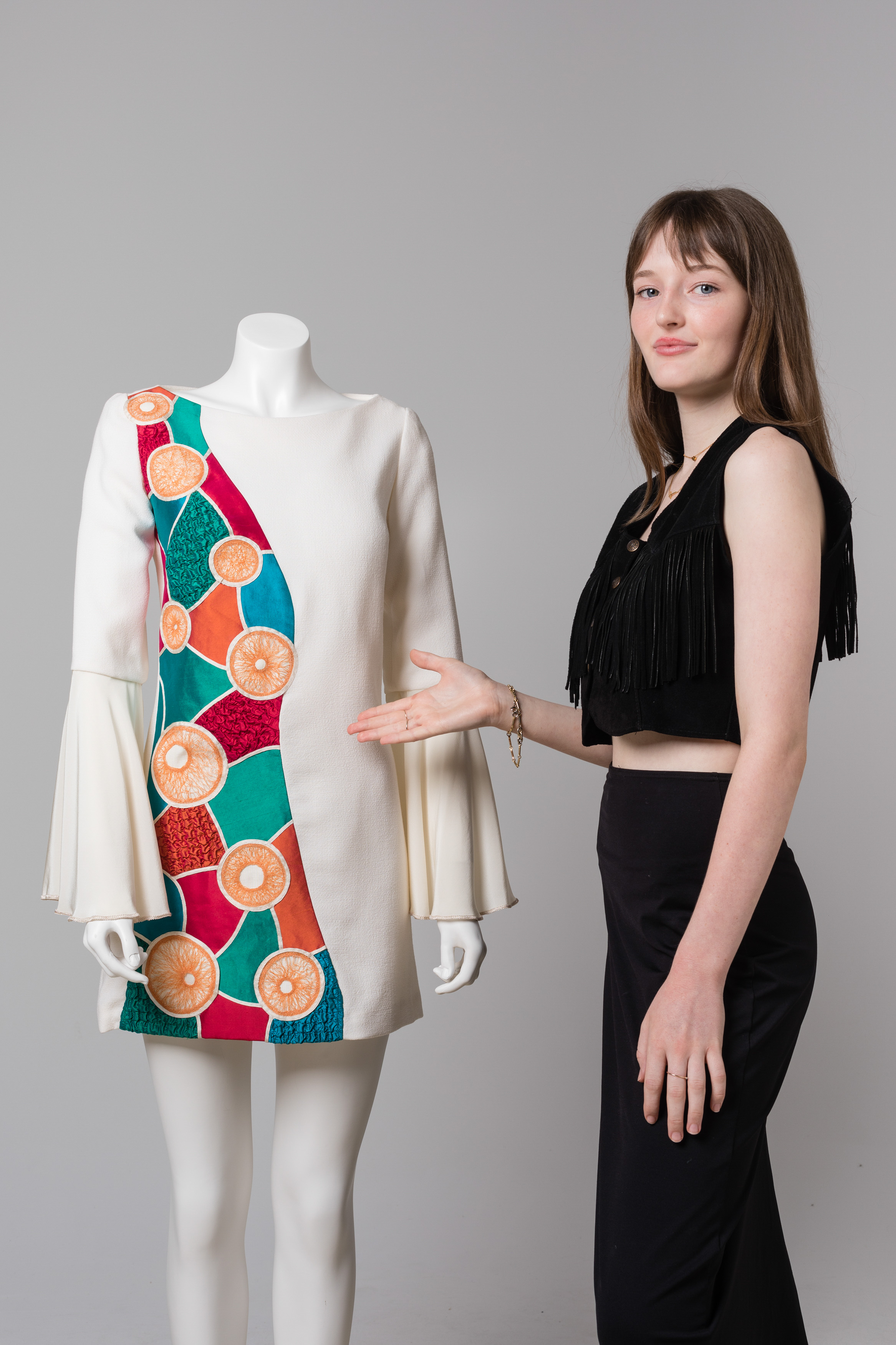 A young woman gesturing to a mannequin beside her. The mannequin wears a long sleeved dress with a colourful pattern down one side and white fabric on the other.