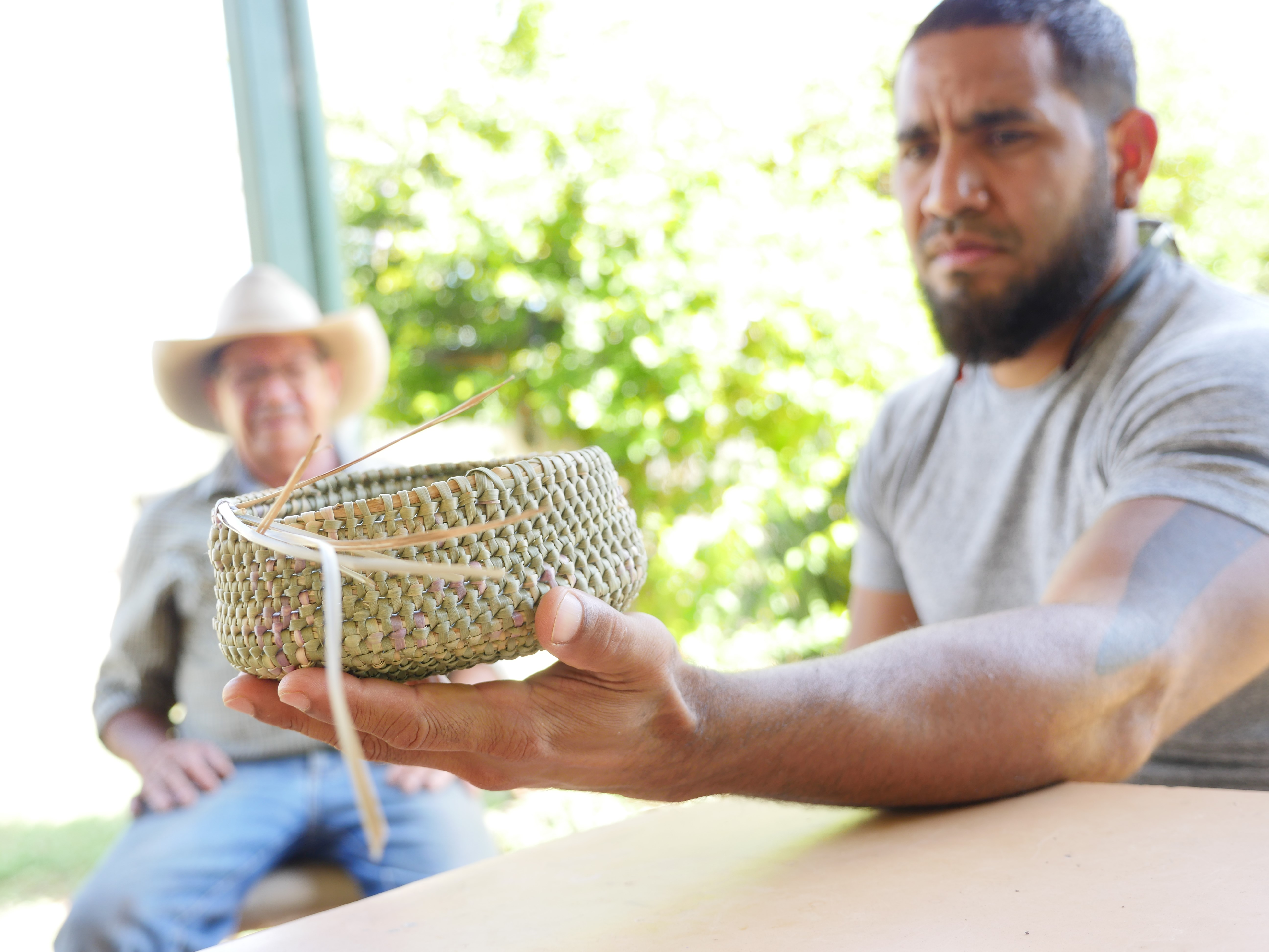 young indigenous man holding woven basket with older indigenous man sitting in the background, both men are out of focus