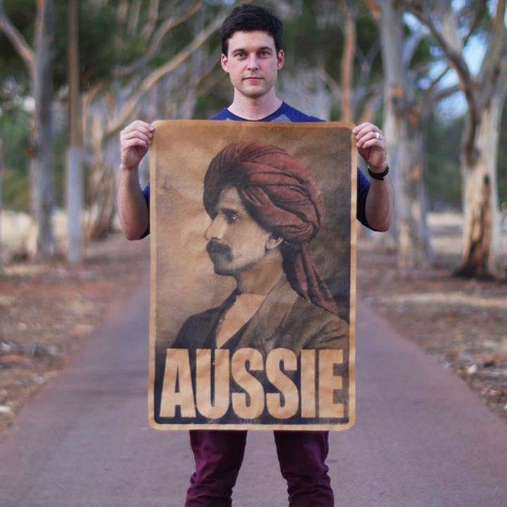 Photograph of a man standing holding a large poster. The poster depicts the portiat of a man wearing a red turban with a moustache and the word aussie appears in large text across the bottom