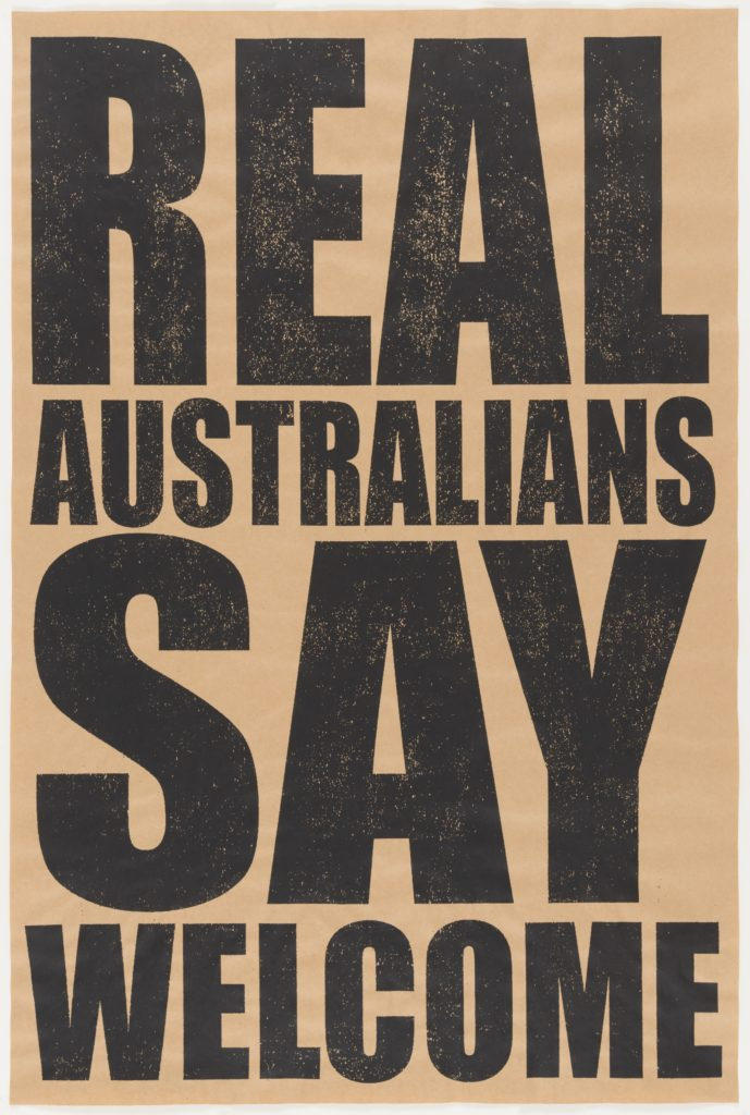 A brown screen printed poster with black capital letters that read 'REAL AUSTRALIANS SAY WELCOME'.