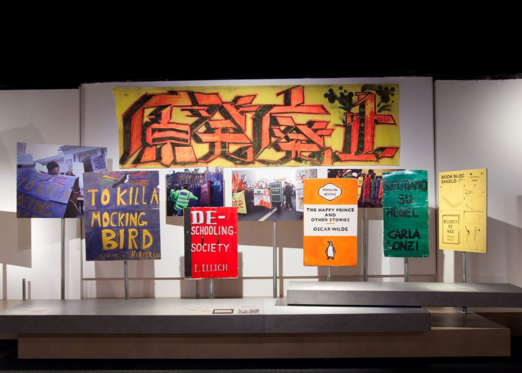 An installation view of Disobedient Objects exhibition at the Powerhouse museum, with a display of protest placards and banners