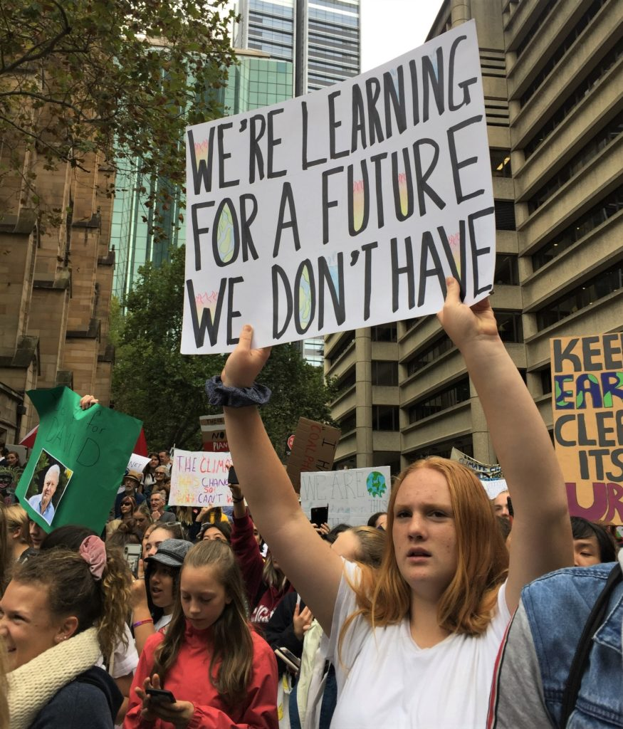 A teenage girl holding a hand-written banner amongst a crowd of people at Sydney Town Hall protesting against inaction on climate change. The banner reads 'We're leaning for a future we don't have'.