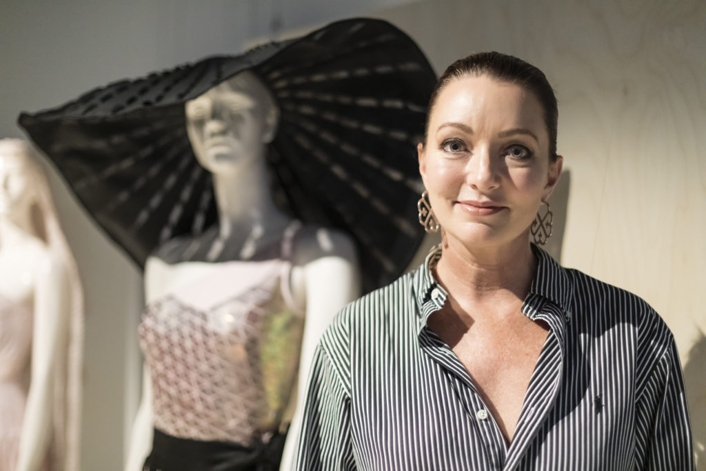 Smiling woman with her hair pulled back in a pony-tail standing in front of a mannequin dressed in a large brimmed hat and sequinned bodysuit; the mannequin is out of focus.