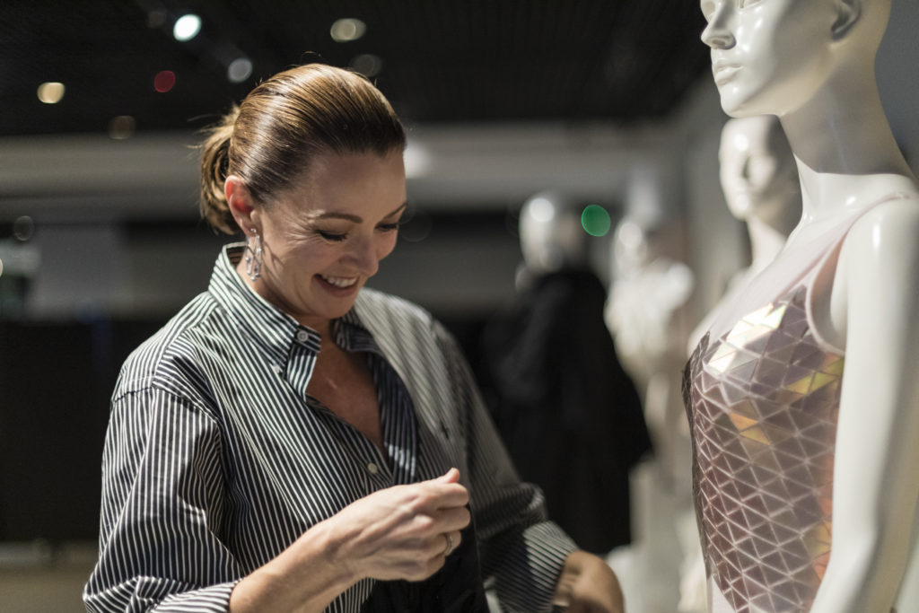 Smiling woman with her hair pulled back in a pony-tail, holding a large hat while standing in front of a mannequin she is preparing to dress.