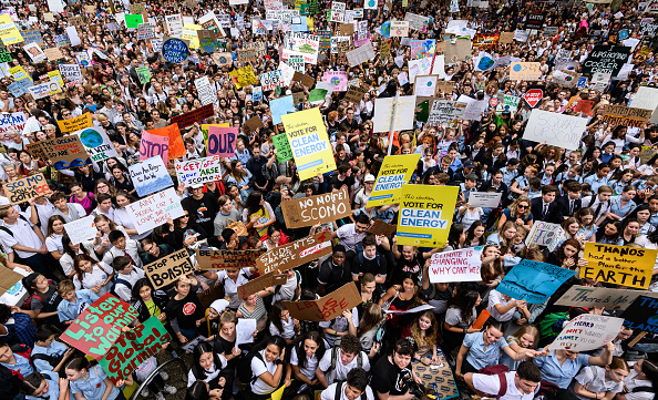 A large crowd of people holding banners and placards at Sydney Town Hall who are protesting against inaction on climate change