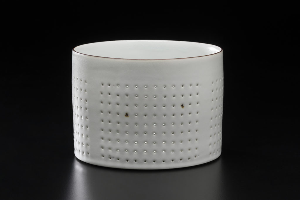 A white cylindrical box in white porcelain decorated with rows of small holes. The top edge and two holes show delicate rust-like brown stains.