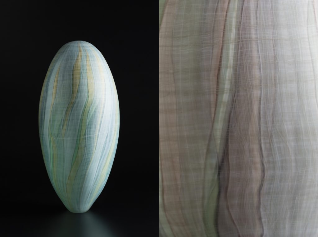 Side view of green glass sculpture set against a black background. The form has a small flat base and a vertical egg-like body with wavy vertical bands of blended green and blue colours.