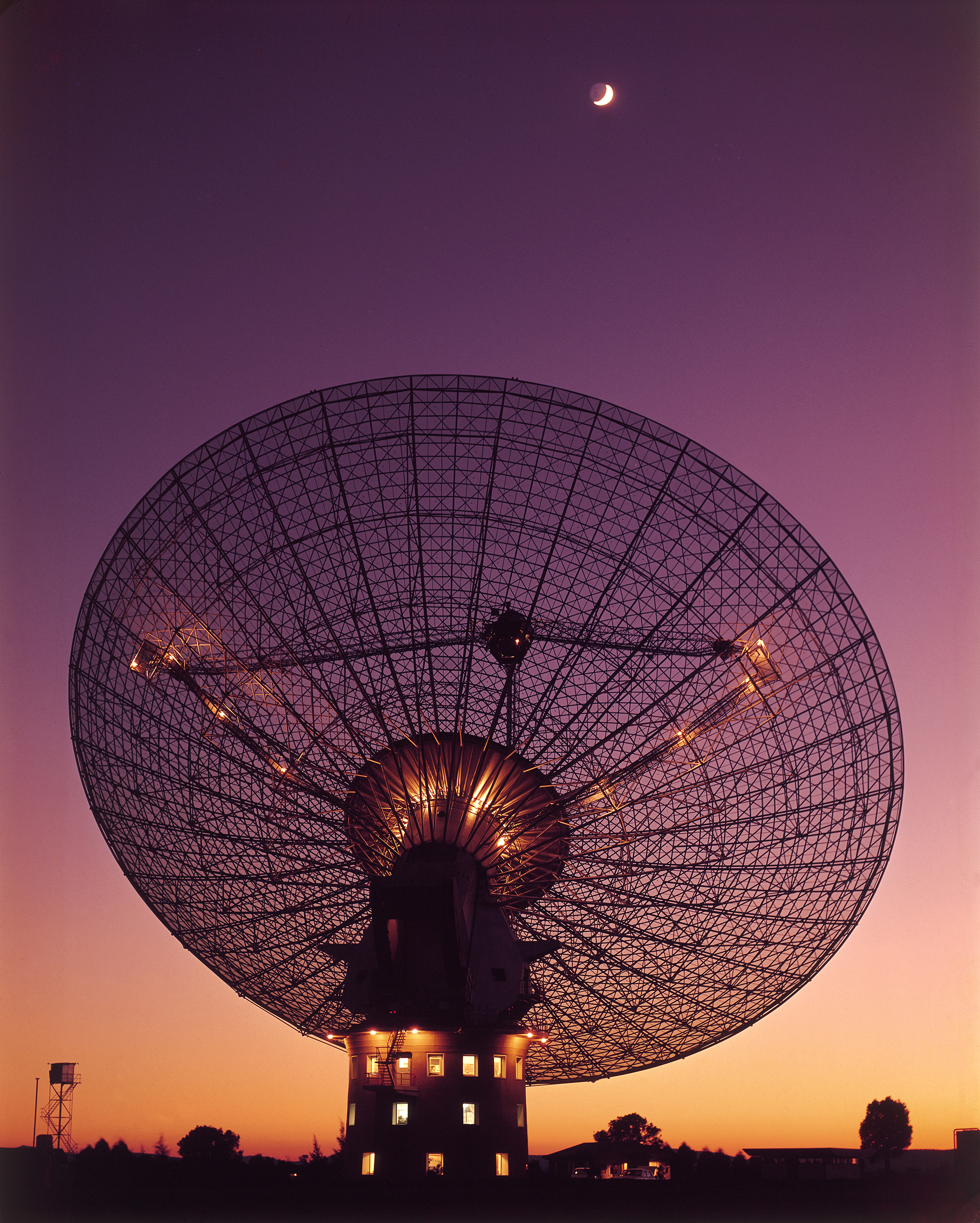 The silhouette of a large radio telescope dish at sunset. The Moon is high in the sky above it.