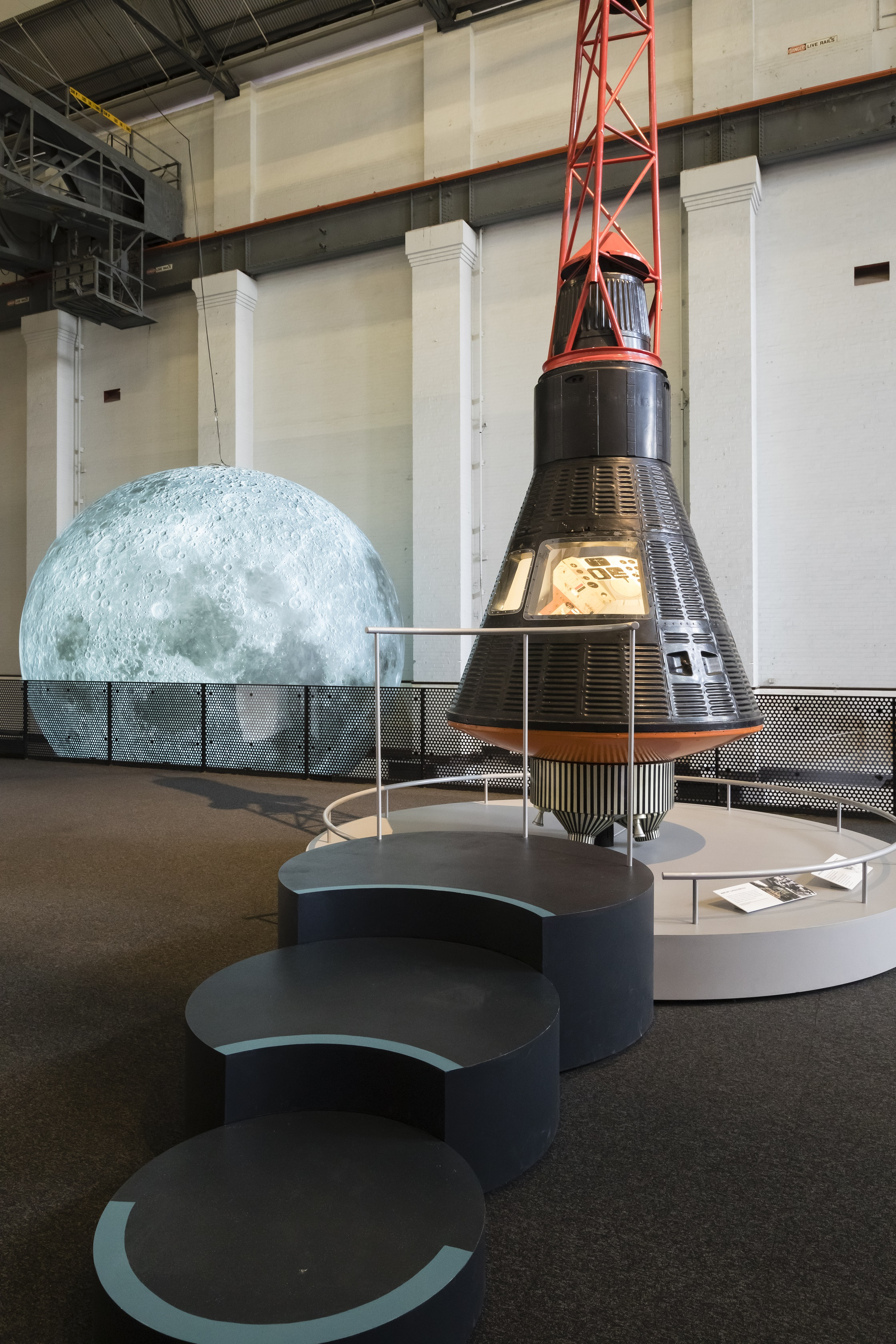 A conical shaped spacecraft with large circular steps forming a viewing platform in front of it.