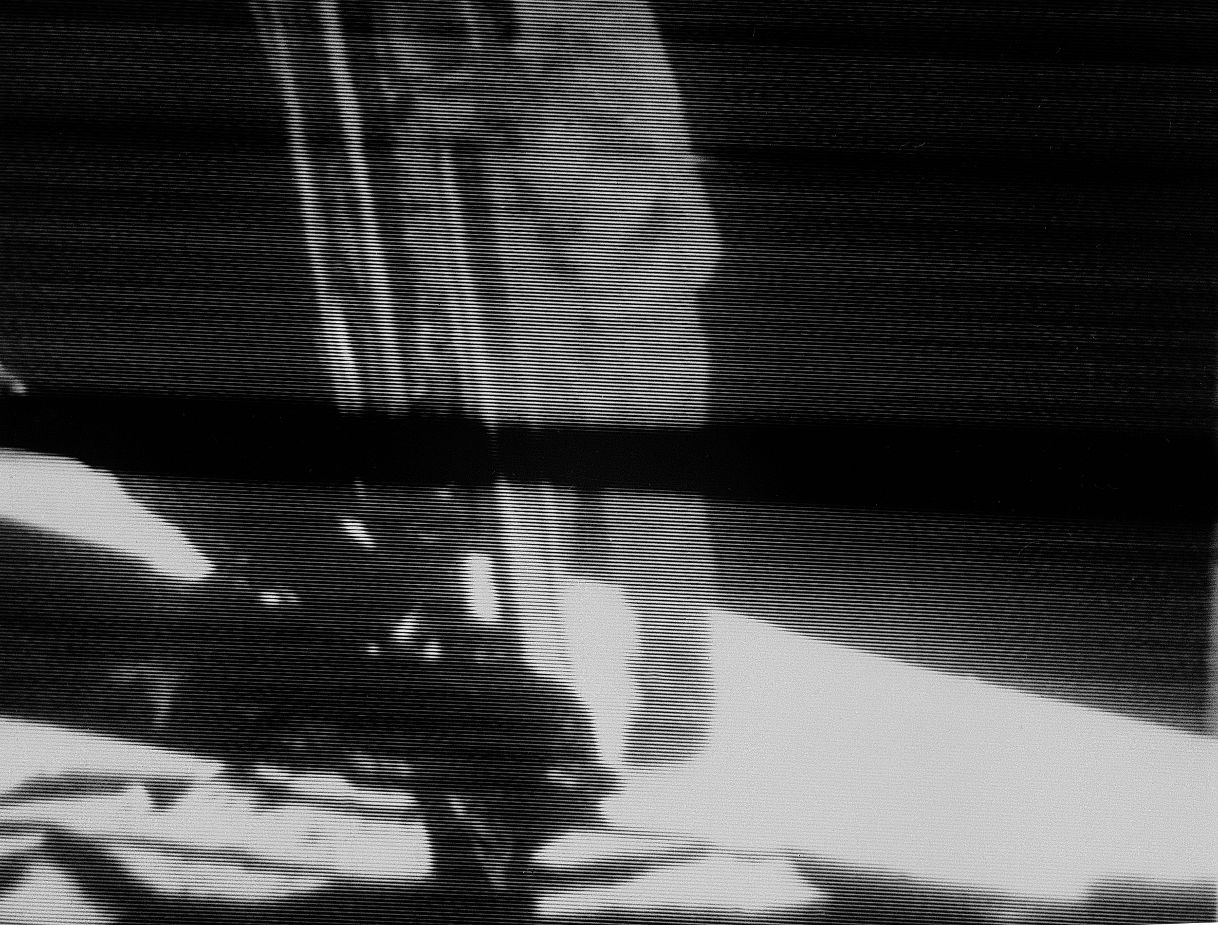 A poor quality black and white image of a man standing coming down a ladder.