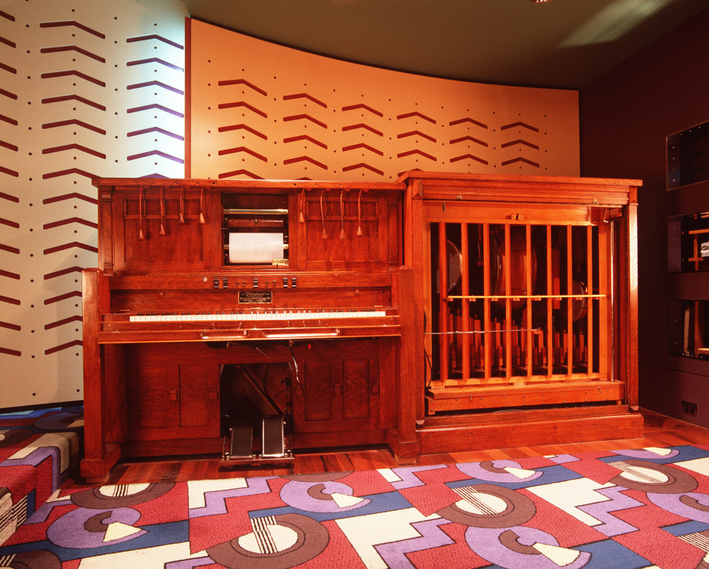 An upright piano attached to a large wooden case, of the same height, containing a variety of musical instruments. At the base of the piano are two large pedals, and above the keys is a scroll of music with four leather pulleys on either side.