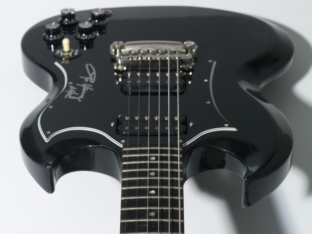Electric guitar with black enamel-finish body and a dark brown timber neck. The body has two volume and two tone control knobs and a toggle switch. The guitar is viewed along the neck looking towards the body.