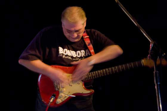 A man wearing a black tshirt reading 'BOMBORA' and playing a red electric guitar. His arms are blurred due to motion.