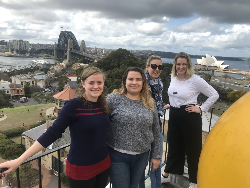 Four women pose for a photo on a high balcony with the Sydney Harbour Bridge and the Opera House in the background. In the foreground is visible part of a very large yellow ball.