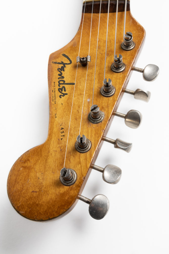 Detail of a Fender Stratocaster headstock. The headstock is made from a mid-coloured wood. There are six tuning pegs along the top, to which are attached six metal strings and a Fender logo along the bottom in the original 'spaghetti' style font.