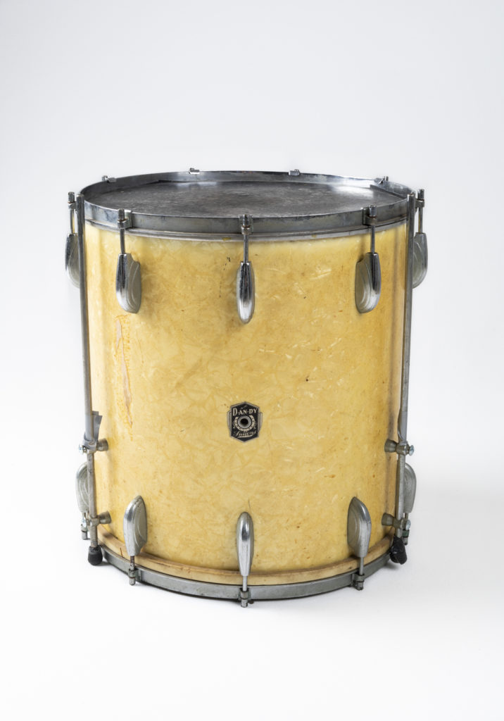 Floor-tom featuring a pearl celluloid laminate over the plywood shell. There are chrome-plated fittings running around the circumference of the drum at the top and bottom. A badge features the Dandy logo with the words 'Supplied by Suttons Pty Ltd'.