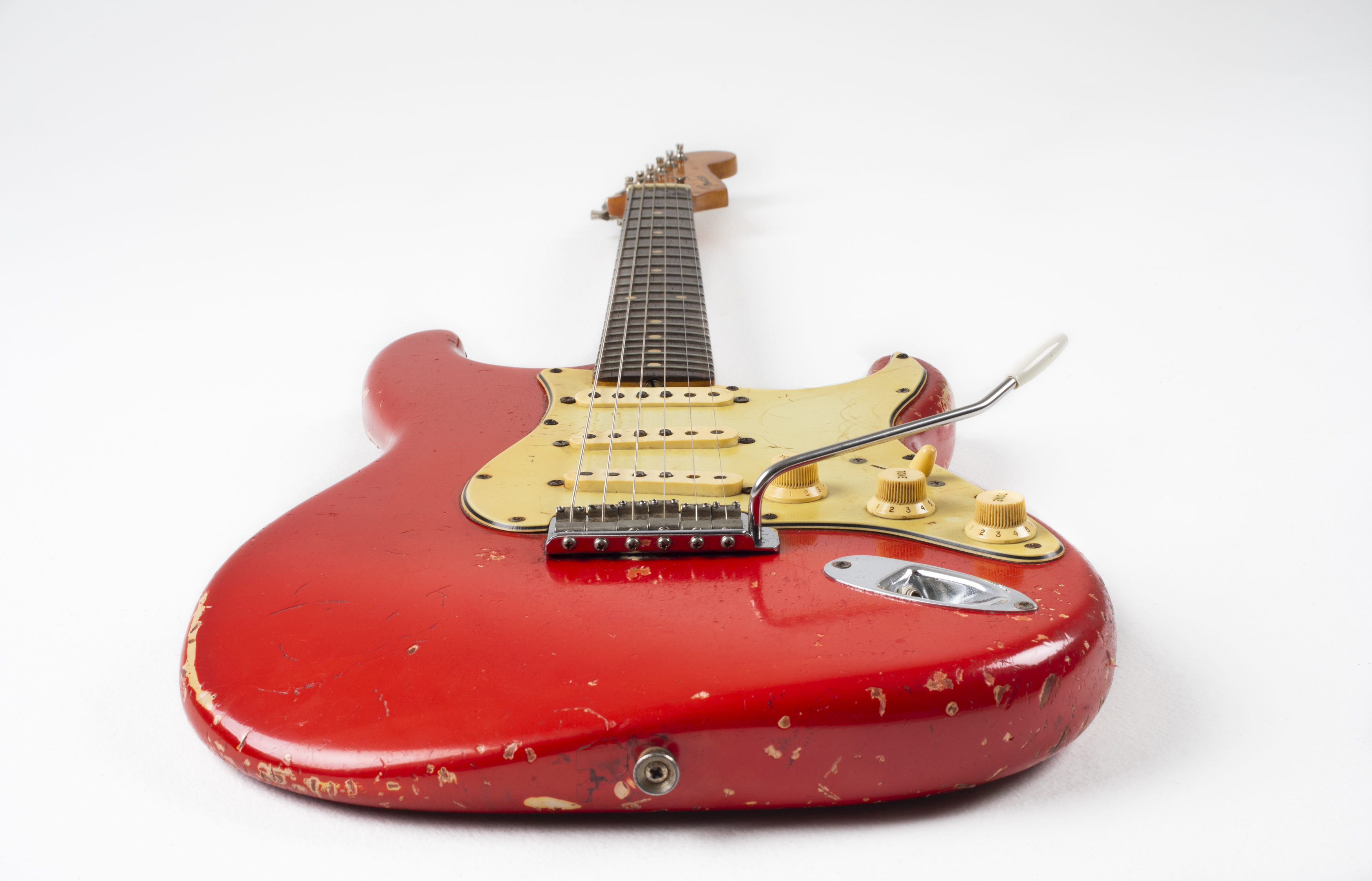 Electric guitar with 'Dakota red' body, cream pick-guard and dark rosewood fret-board. The guitar is viewed from the body along the neck towards the headstock. The body has severe road-wear.