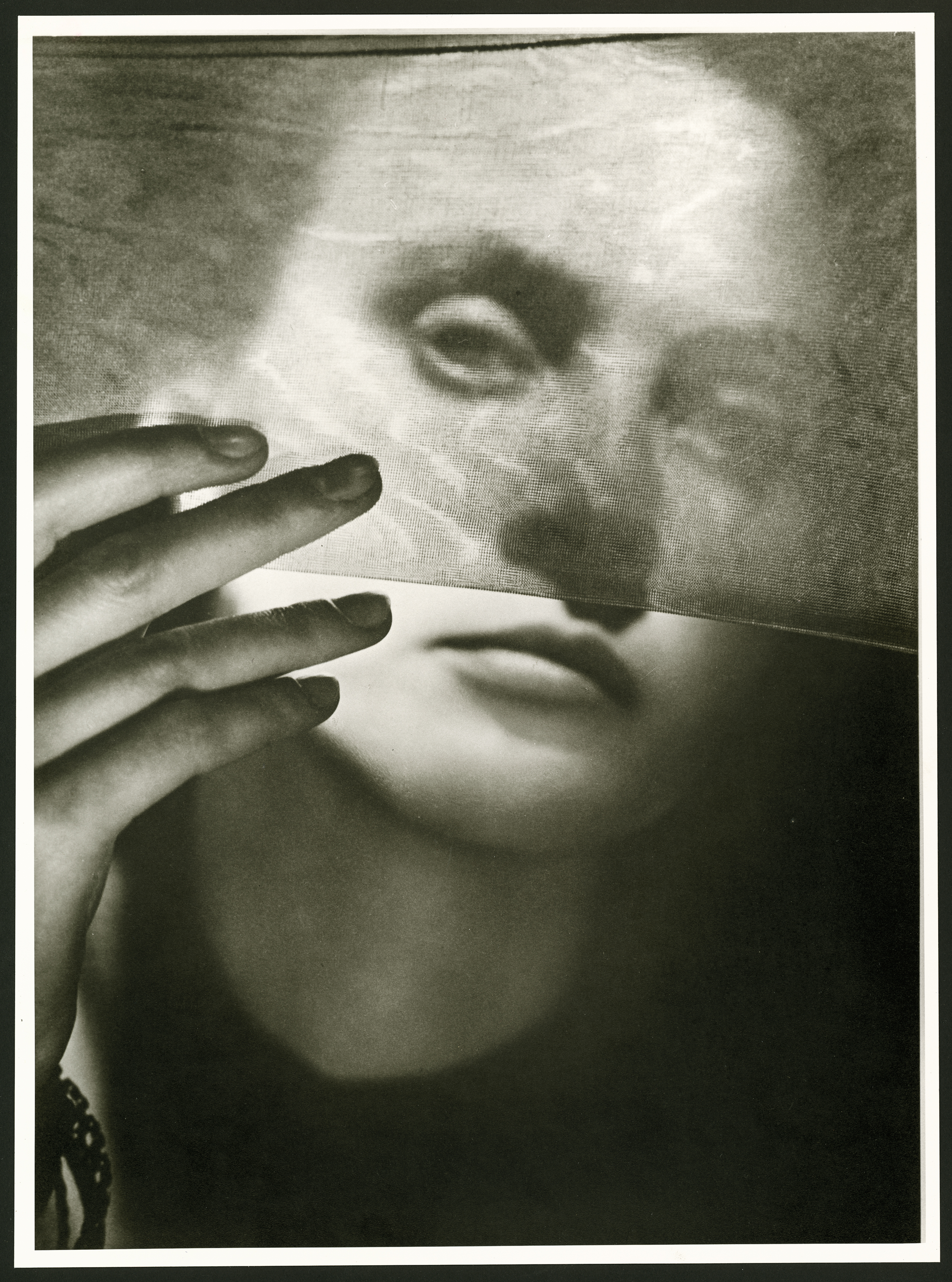 Black and white photograph showing face of a young woman holding in her hand a section of a stretched nylon stocking which covers top part of her face like a thin veil.