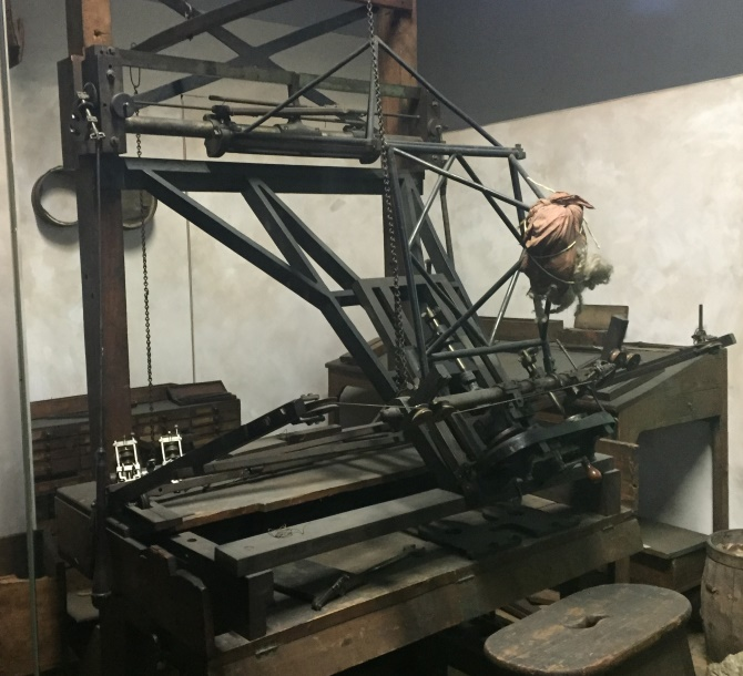 A complex machine with a metal frame comprising various rods, wires, chains and pulleys. It's not obvious how it worked, but the viewer can imagine a pointer following the contours of a statue and controlling a cutter to create a copy.