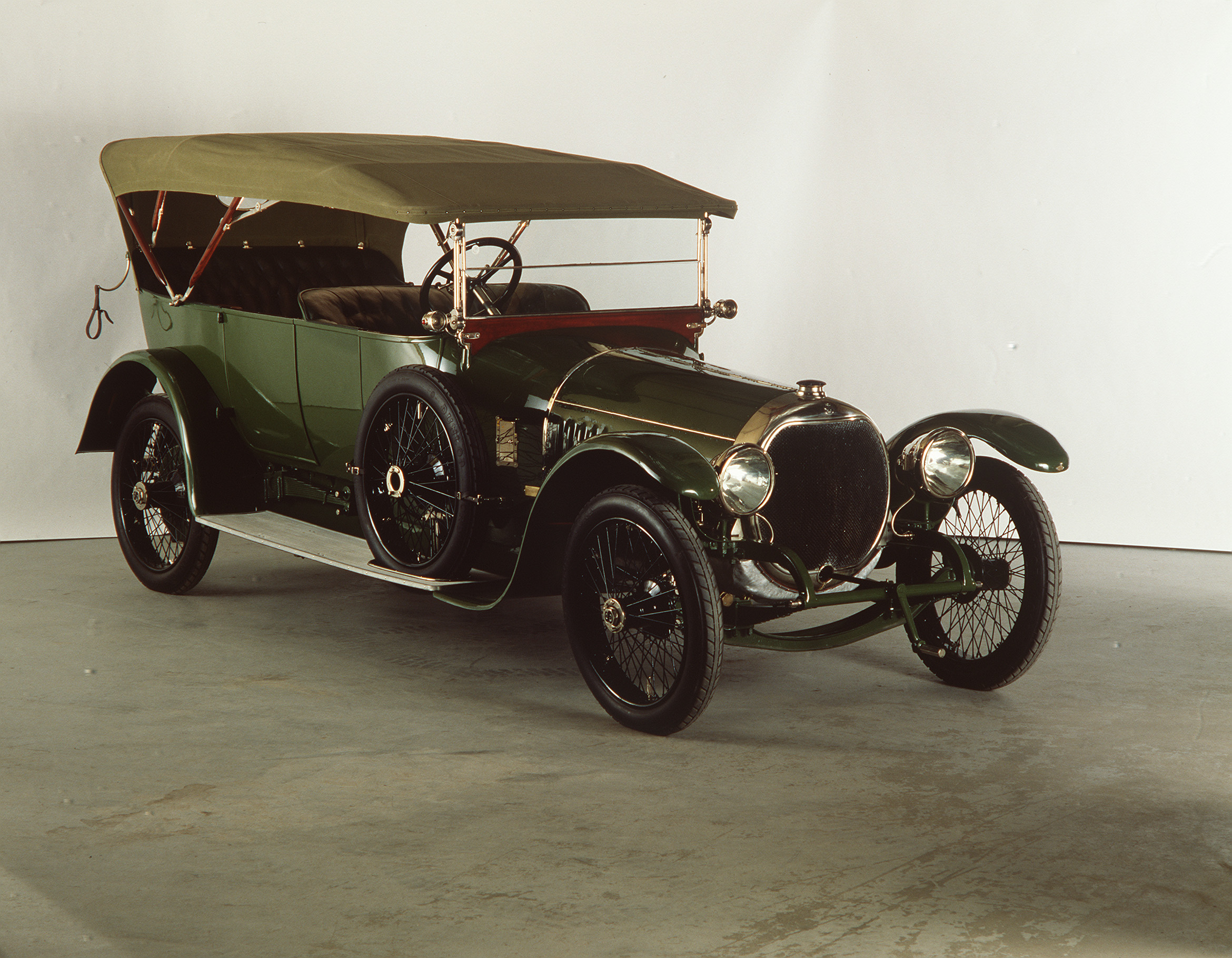 A black and green 1910s-era car with an open-top carriage and convertible roof-covering. The wheels of the car are very narrow yet have a wide diameter giving the car a high-set seating carriage.
