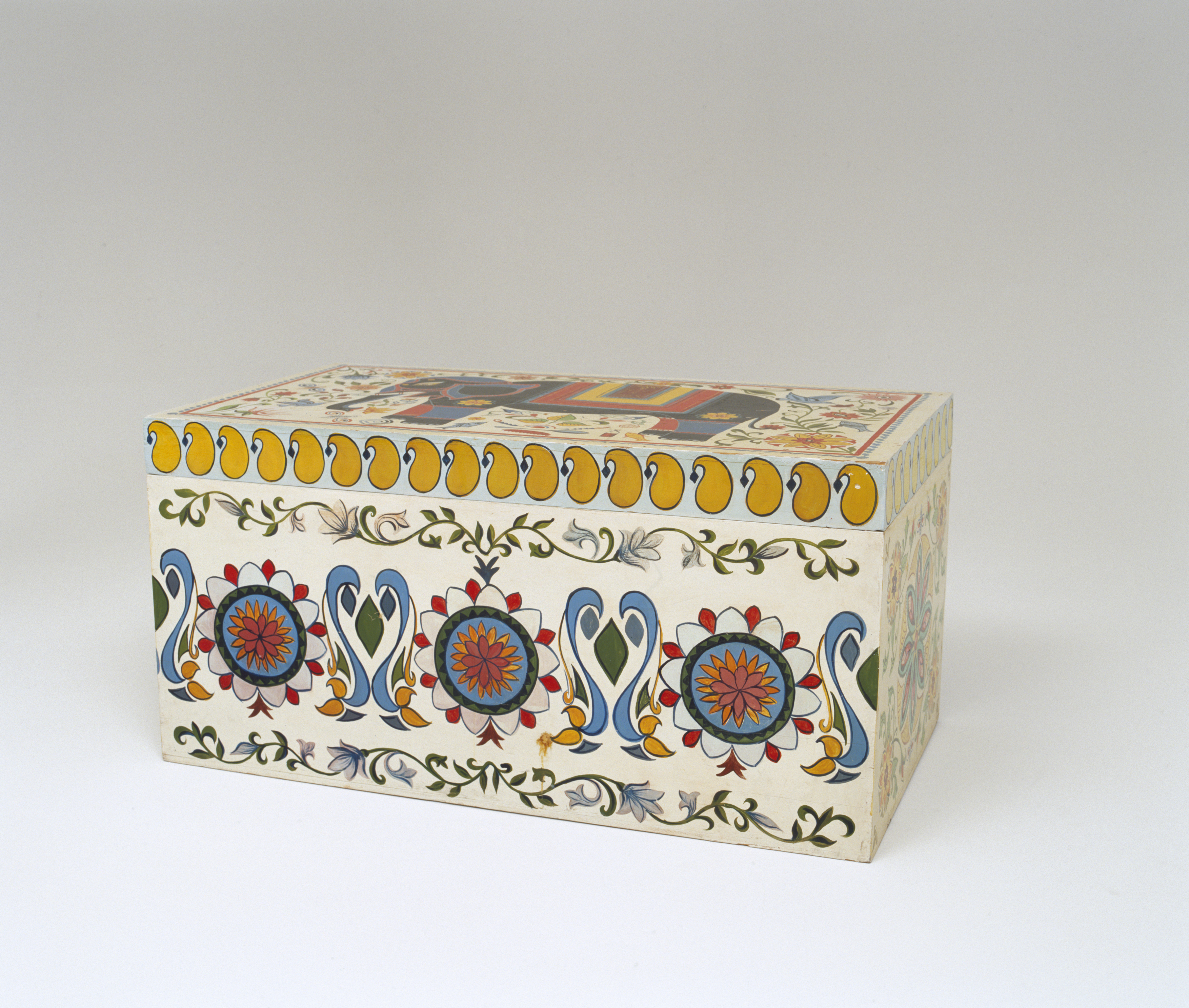 Wooden linen chest hand-painted to match the nakshi kantha. It is decorated on the top and all four sides. On the top is a black elephant with yellow red and blue trappings surrounded by flowers, leaves, fish and some articles of everyday usage. The border is a red line with a blue 'ribbon' pattern outside it. Each end of the box is decorated with a stylised lotus flower in the centre surrounded by more flowers, leaves and insects. On the front of the box is a whole row of stylised lotus flowers surrounded by swirling fronds of vegetation. There is a row of yellow boteh (in Bangladesh, kalka) around the top.