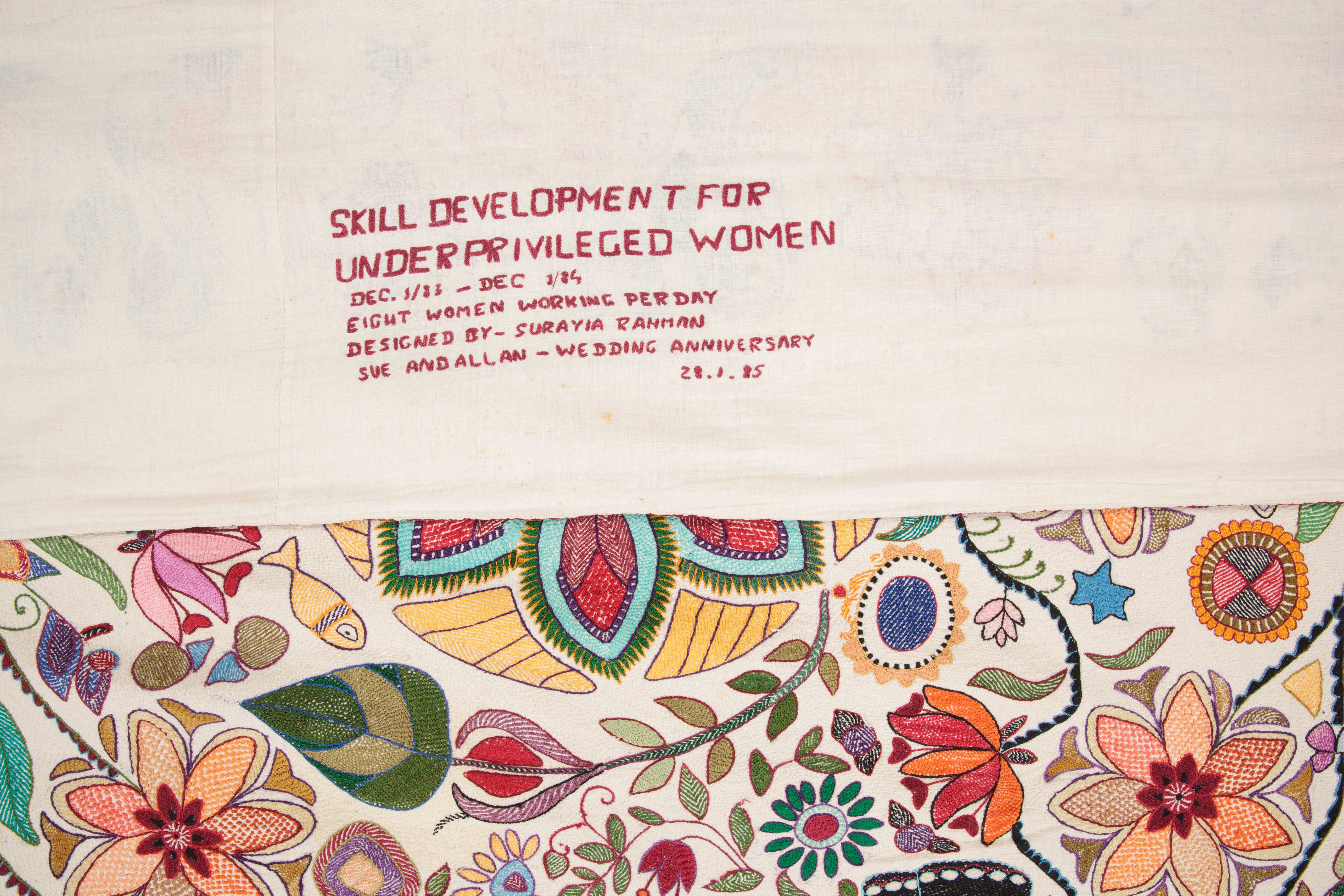 Close up of the production and provenance information embroidered on the reverse. Text says 'Skill Development for Underprivileged Women. DEc 1983 - Dec 1984. Eight women working per day. Designed by Surayia Rahman. Sue and Allan - Wedding Anniversary. 28.1.85'
