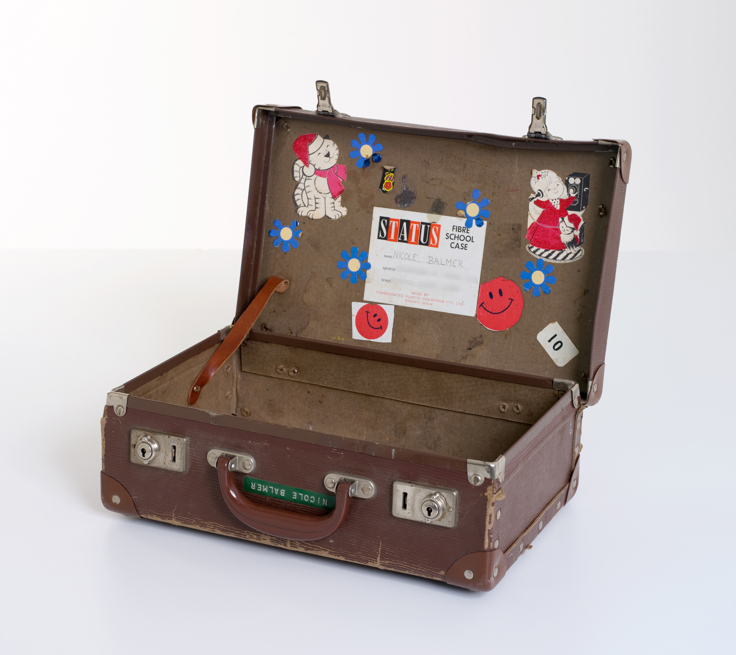 A brown, rectangular leather school case (open). The name 'Nicole Balmer' is marked next to the handle in Dymo tape, and the inside of the lid is covered in stickers.