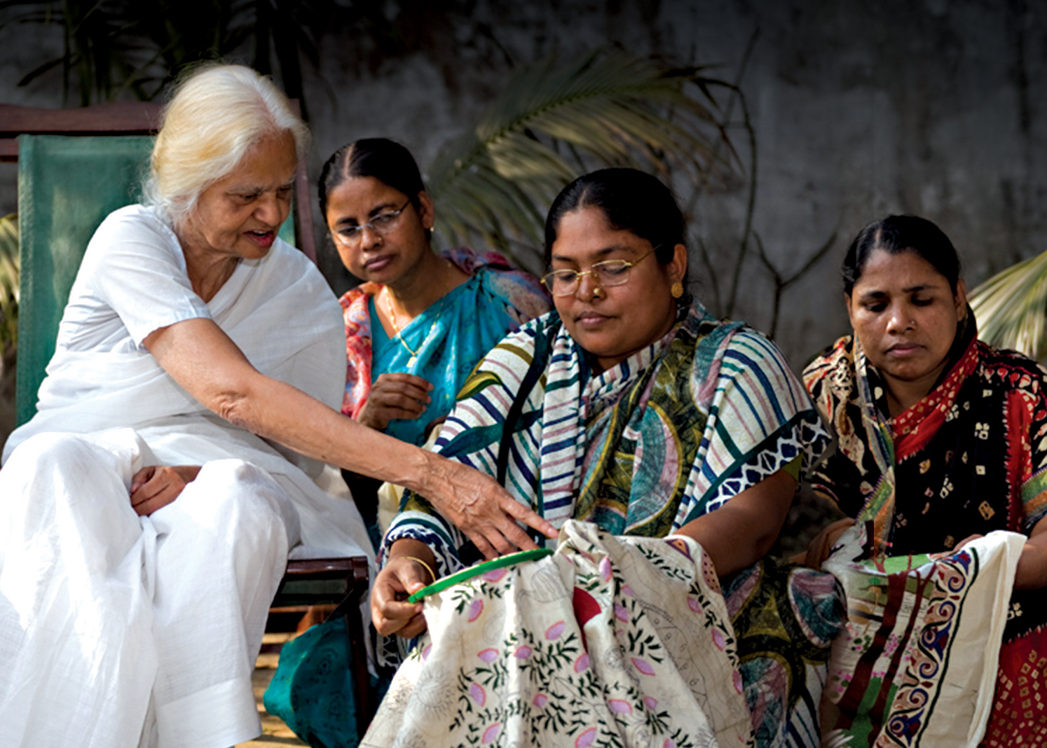 Image of Surayia Rahman with three fellow artisan embroiderers. One woman has an embroidery hoop and Surayia is seen guiding the embroiderer while the other two women watch.