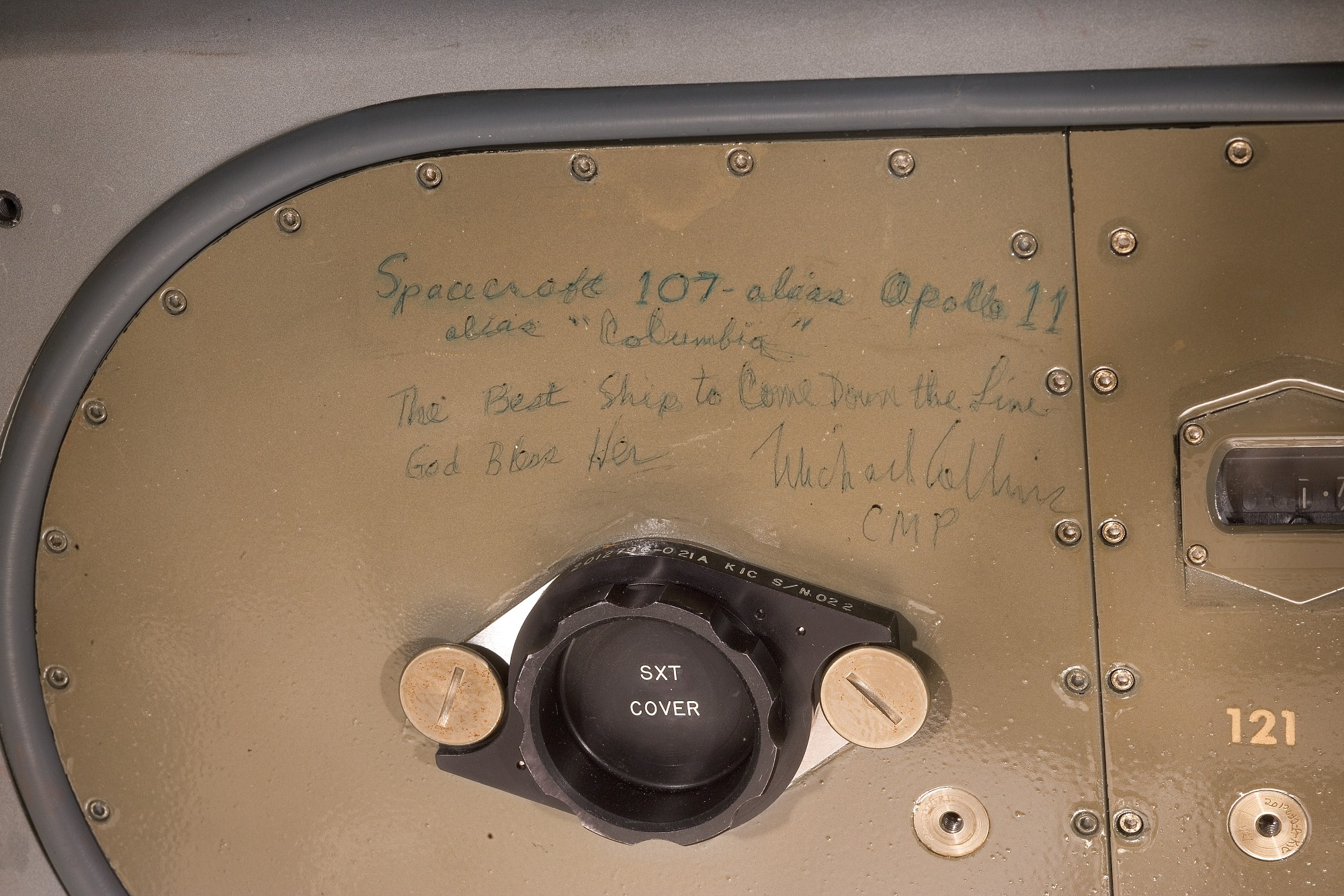 """Metal panel with rivets around the edge. Handwritten text in green ink reads: 'Spacecraft 107 – alias Apollo 11 / alias """"Columbia"""" / The Best Ship to Come Down the Line / God Bless Her / Michael Collins / CMP'."""