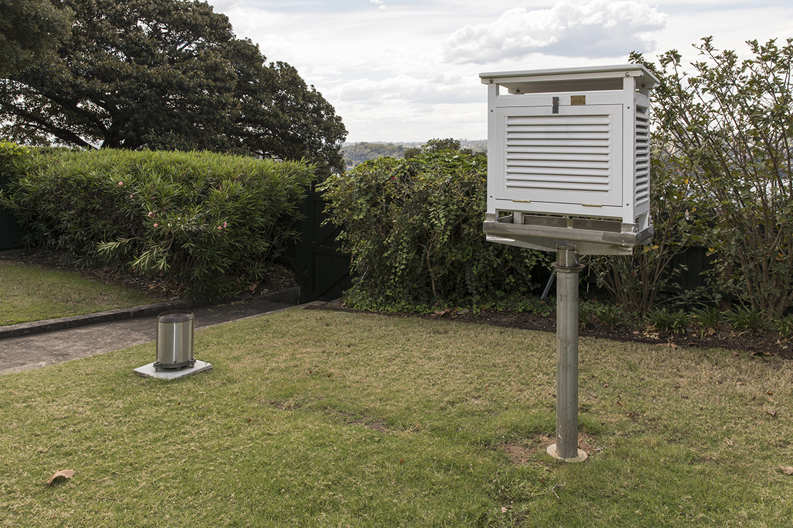 Lawn area in which is mounted a white box, approximately 40-50cm in size, on top of a metal post. The four sides of the box have louvres, fixed on an approximately 45 degree angle.