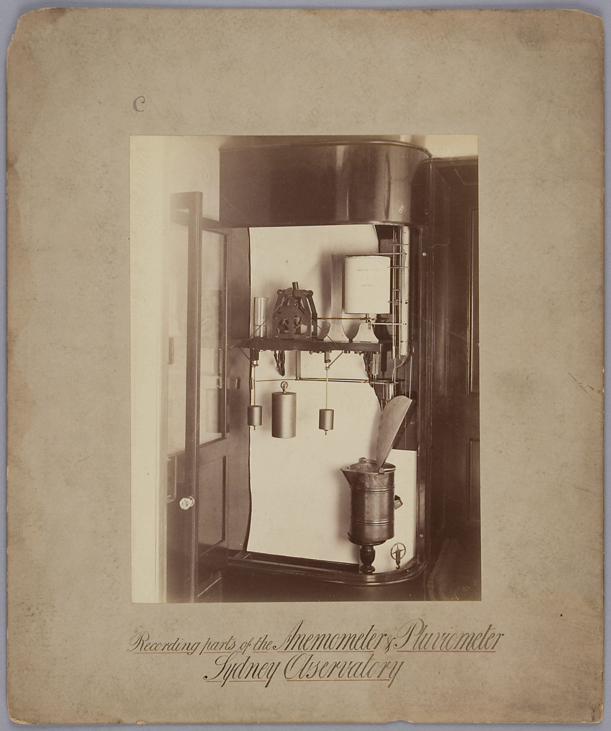 Sepia-toned photograph mounted on an aged piece of paper. The photograph depicts complex measuring machine, approximately as tall as a person, with various weights, pulleys, a water-collecting container and a rolled measurement chart.