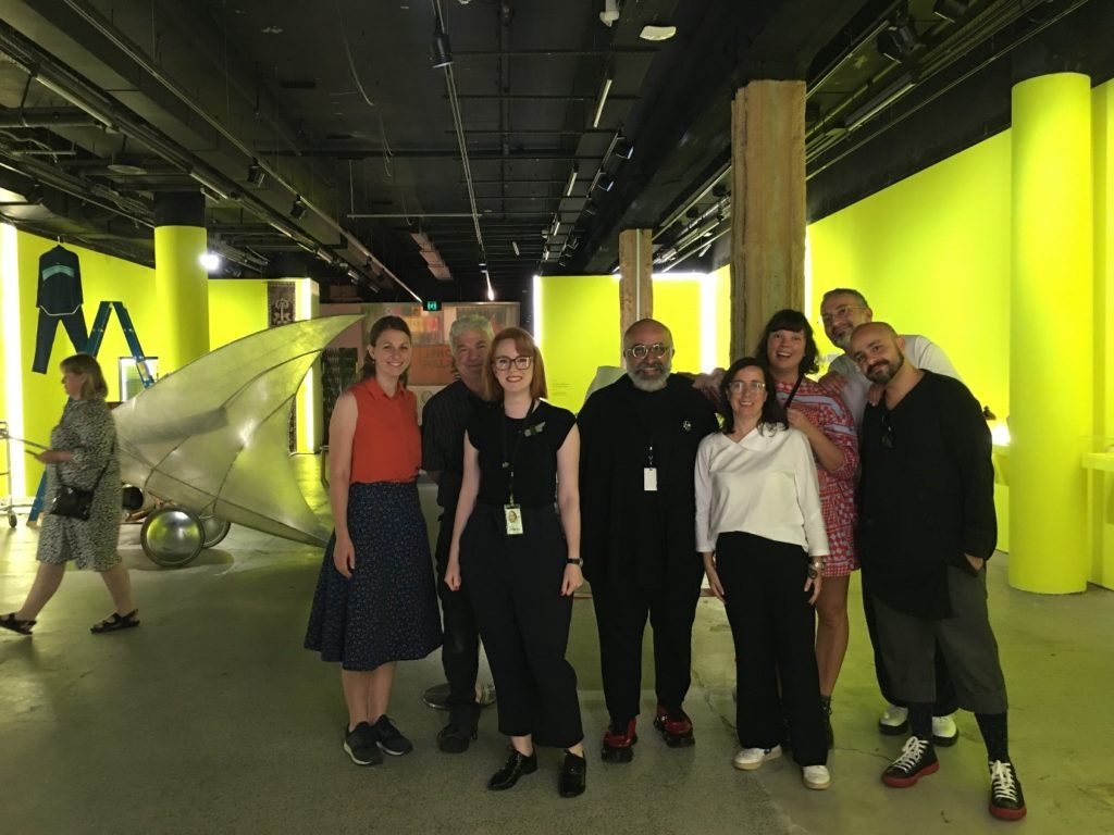 Photo of a group of staff in the gallery space. The walls are painted fluoro yellow and a variety of Museum artefacts and a ladder can be seen in the background.