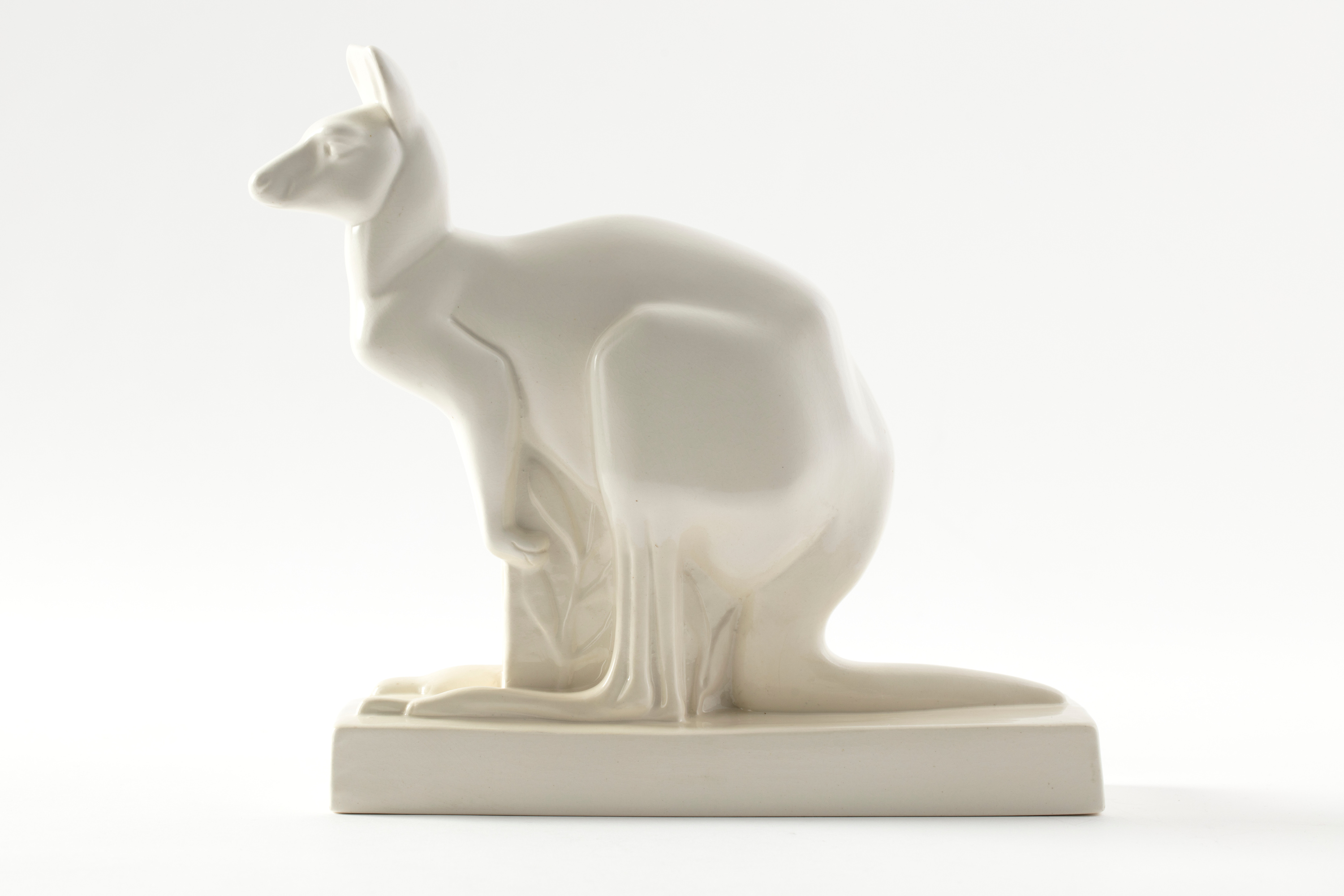 White earthenware kangaroo on a white studio background. The kangaroo has a minimalist form, sits on a rectangular base, and is lit by soft lighting.