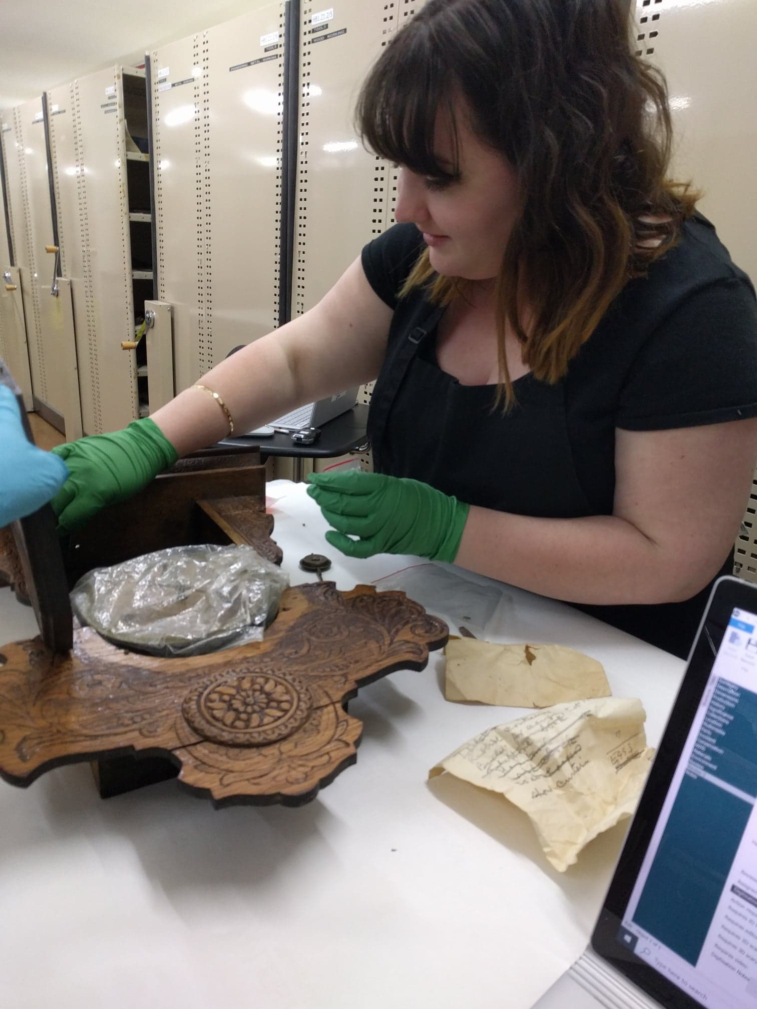 A woman wearing latex gloves in the process of cleaning a carved, wooden collection item. There is a dramatic difference between the cleaned and uncleaned areas, with a dark coating of dust having been removed. Behind her is a row of compactus bays.