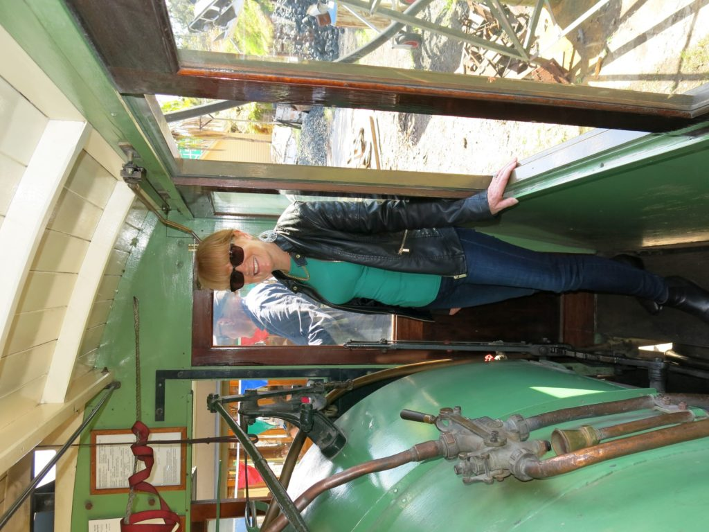 A woman wearing jeans and a leather coat is standing on a narrow wooden platform inside a steam tram. To her right is the side of a boiler and to her left are two windows. A steam tram is like a steam locomotive which travelled along streets. A wooden cab enclosed the entire locomotive, which features five windows along each side. Access to the cab is through doors from either a front or back platform.