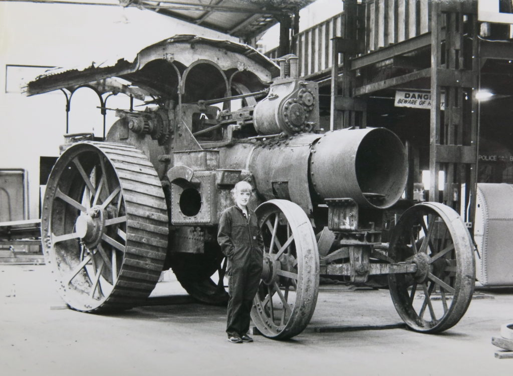 A woman wearing overalls is standing inside an old factory building in front of a large steam traction engine which has a canopy roof. A traction engine is a self-propelling steam road vehicle. The fuel was burnt and steam raised in a locomotive-type boiler.