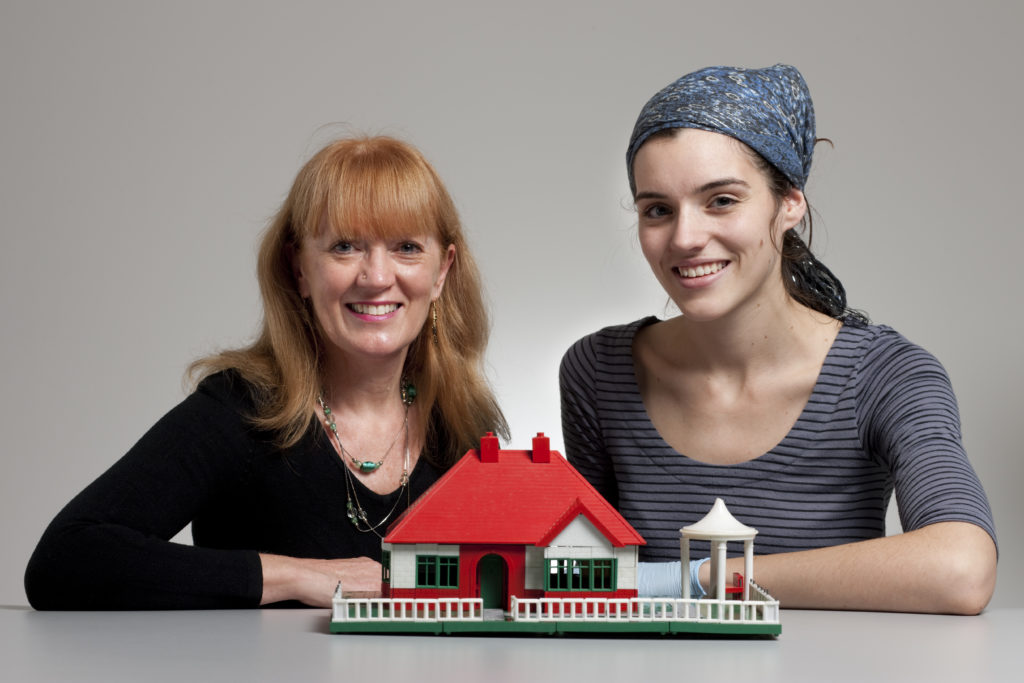 Two women sit at a table behind a toy house made of plastic construction bricks. It is a high-roofed single-storey house made up of red, green and white 'BAYKO' parts with a lawn, white fence, path and a small gazebo to the house's right.