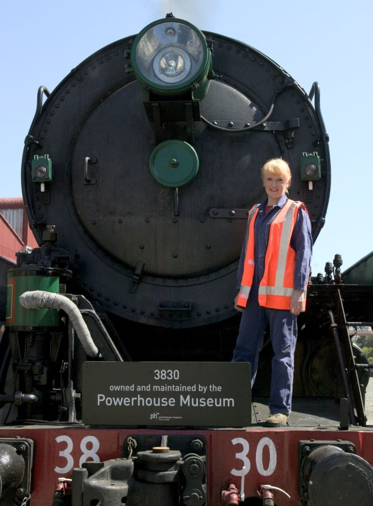 "A woman wearing overalls and a 'high-viz' vest is standing on the front of a huge steam locomotive which is in steam. A board on the front of the steam locomotive has the wording ""3830 owned and maintained by the Powerhouse Museum""."