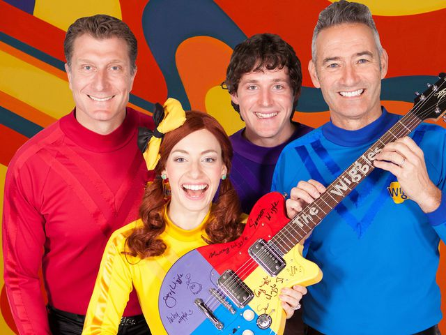 The Wiggles smiling together, holding an electric 'Wiggles' guitar covered in signatures