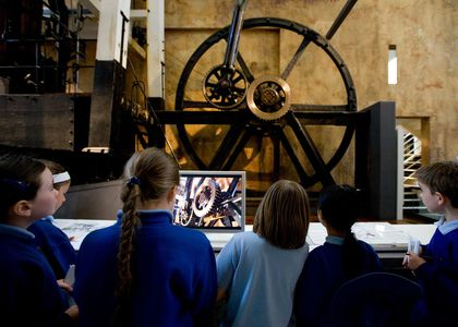 School children standing with backs to the camera, looking up at the Boulton and Watt Engine display